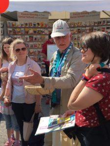 Ehrenbotschafter Manfred Holz erklärt Besuchern den fairen Handel