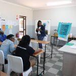 Erwachsene sitzen in einem Klassenraum und lauschen einem Vortrag.