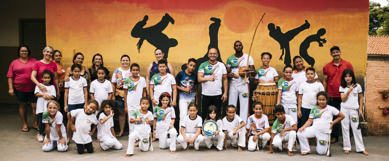 Eine Capoeira Gruppe steht vor einer bunten Wand.