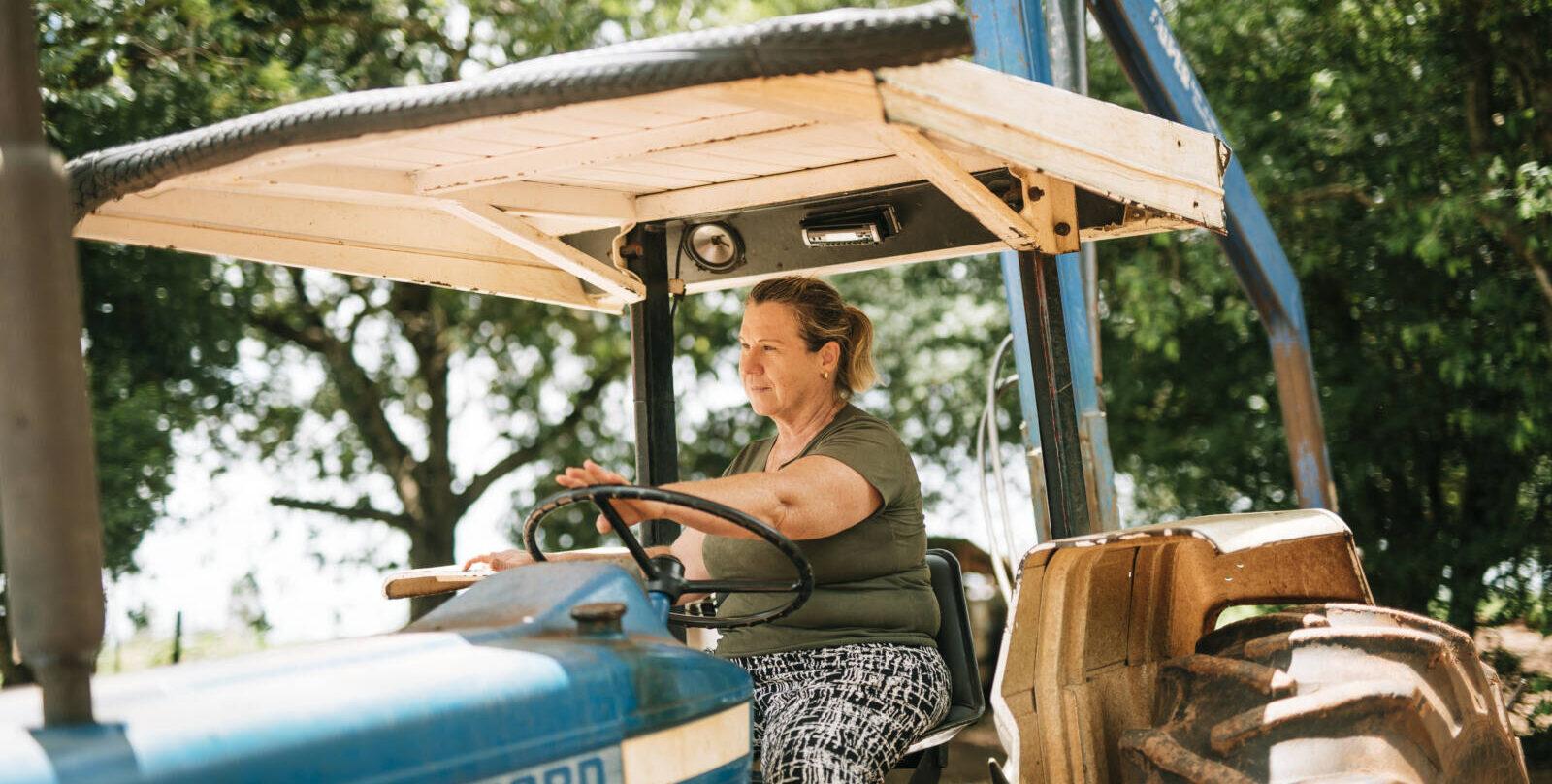 Eine Frau sitzt auf einem blauen Traktor.