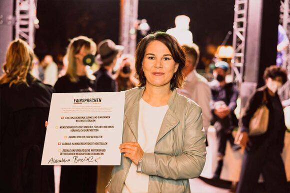 Annalena Baerbock hält das unterzeichnete Fairsprechen in der Hand