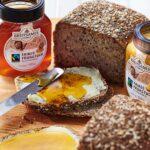 Schraubgläser mit Fairtrade-Honig von Breitsamer auf dem Frühstückstisch ©Breitsamer Honig